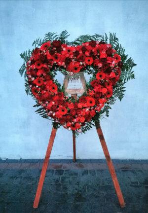 Wieniec pogrzebowy w kształcie serca z naturalnych kwiatów na stojaku